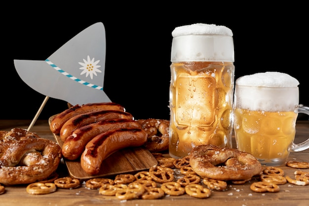 Mugs of beer with sausages on a table