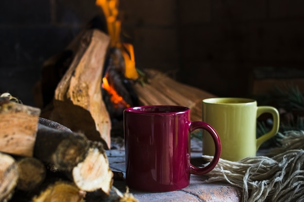 Mugs and blanket near fire in fireplace