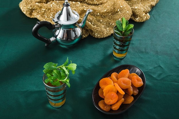 Mugs of drink near silver teapot and dried apricots