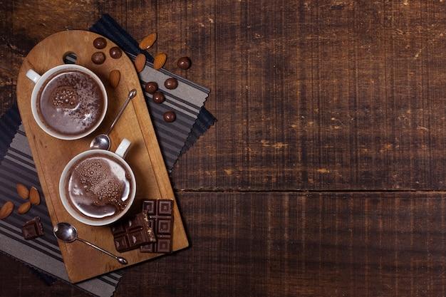 Mugs of hot chocolate on chopping board