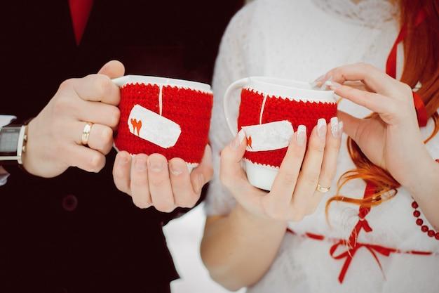 Кружки в красных вязаных чехлах с сердечками с горячим чаем и паром в руках влюбленных