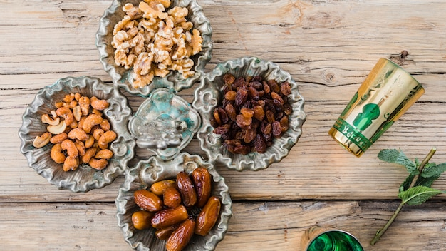 Mugs near plant twig, dried fruits and nuts on board