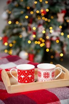 Кружки на деревянном подносе возле новогодней елки концепция уютного домашнего вечера