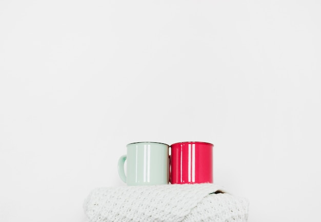 Mugs standing on warm scarf