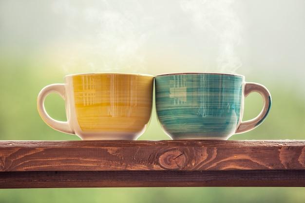 Кружки с горячим напитком с чаем на деревянной подставке на природе в сельской местности