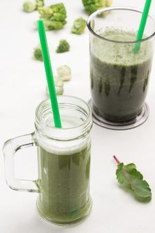 緑の野菜スムージーとマグカップ