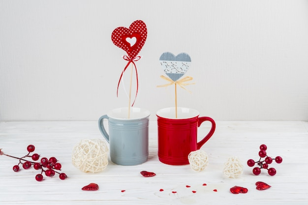 Mugs with hearts on wands near little hearts and berries