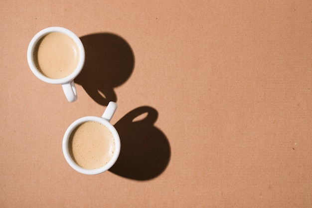 Mugs with hot coffee and shadows