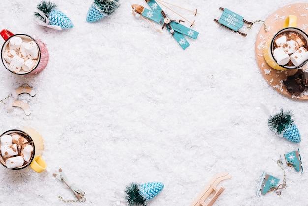 Кружки с зефиром и рождественскими игрушками на снегу