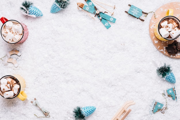 Mugs with marshmallows and christmas toys on snow