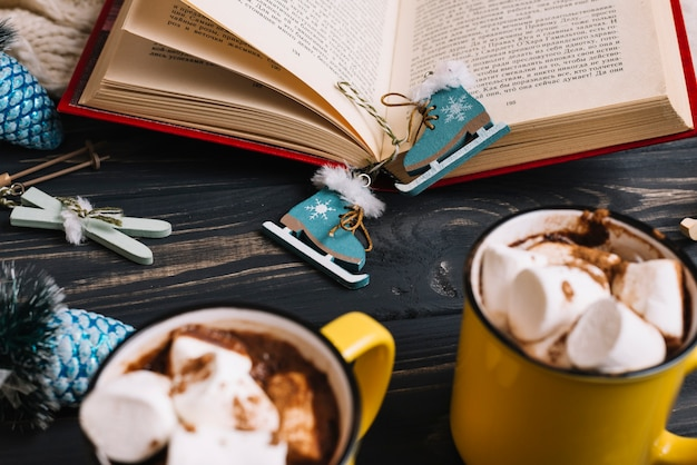 Mugs with marshmallows and drinks near christmas decorations and book