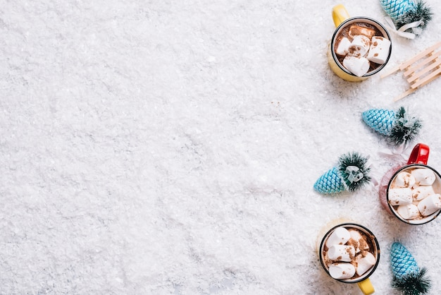 Mugs with marshmallows and drinks near christmas toys between snow