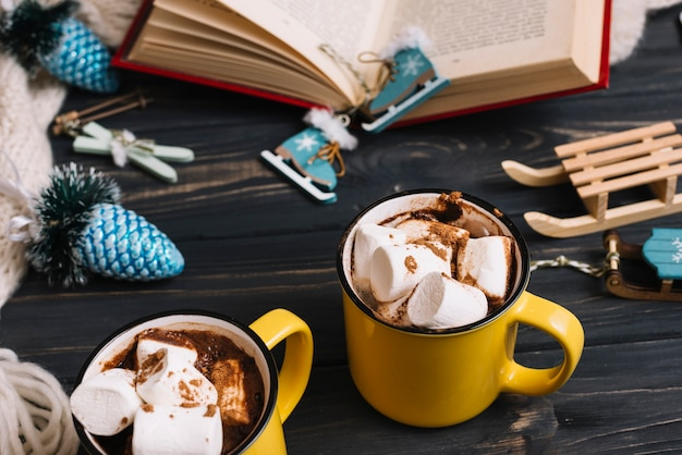Mugs with marshmallows near christmas decorations and book