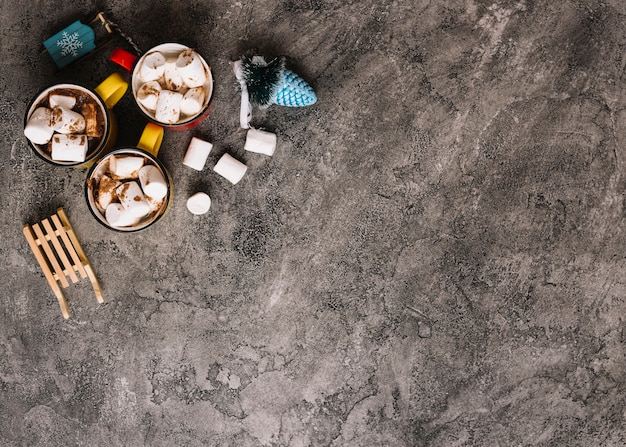 Mugs with marshmallows near christmas toys