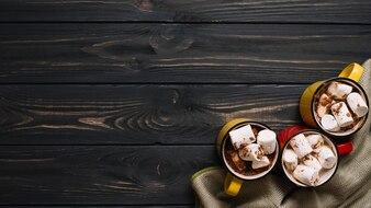 Mugs with marshmallows near cloth