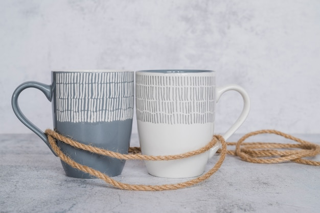 Mugs with rope on white scuffed surface