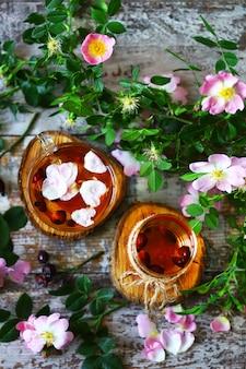 Кружки с шиповником. ветви шиповника. цветы шиповника. лепестки шиповника. здоровый лечебный напиток. летний натюрморт.