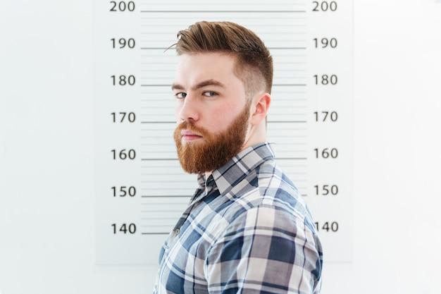 Mugshot бородатого мужчины, смотрящего в камеру