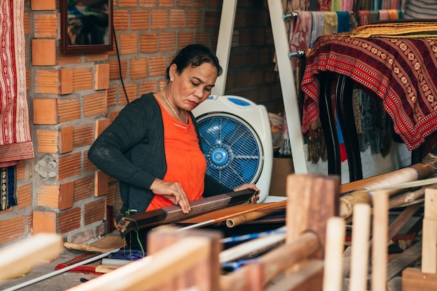 Mui ne, vietnam - march 6, 2017: female weaver working at a traditional weaving machines for silk