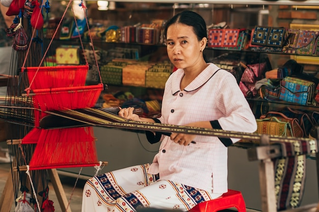 Mui ne, vietnam - march 6, 2017: woman asian weaver working on a traditional loom for yarn silk