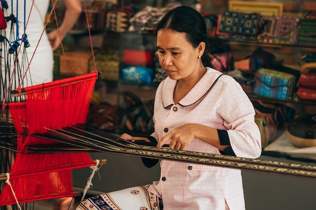 Mui ne, vietnam - march 6, 2017: woman weaver working on a traditional vietnamese weaving loom for yarn silk
