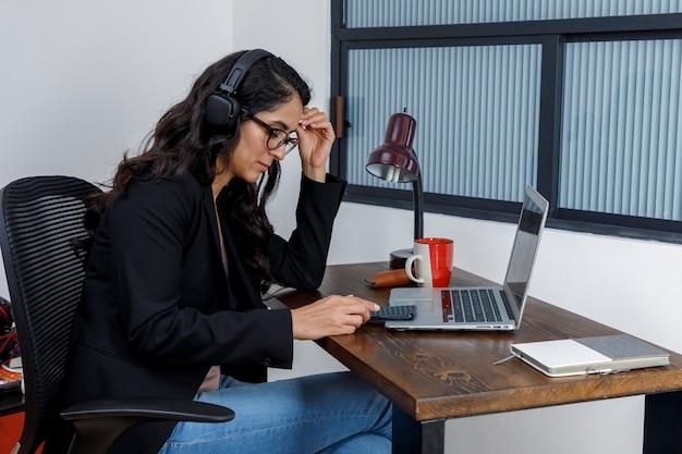 Mujer aburrida revisando sus mensajes de celular mientras trabaja desde casa por la cuarentena