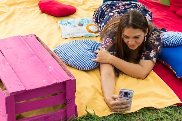 Mujer colombiana acostada en el suelo utilizando el telfono movil ysonriendo
