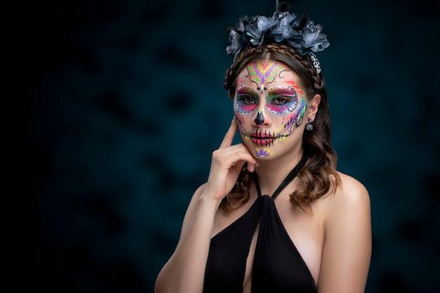 Mujer con maquillaje de catrina tradicional por dia de muertos y usando un vestido negro con fondo