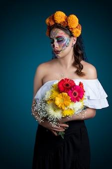 Mujer con maquillaje de catrina y flores en el cabellos usando un vestido blanco dia de muertos
