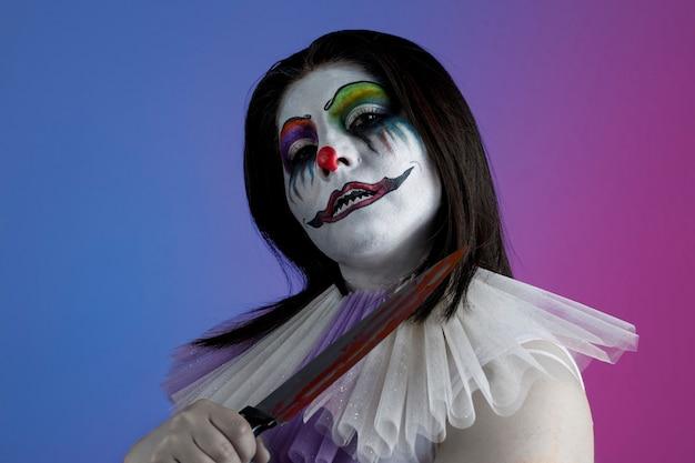 Mujer con maquillaje de payaso y cuchillo en la mano tematica de halloween