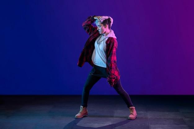 Mujer joven latina con cabello corto y estilo trap bailando y haciendo expresion corporal