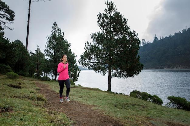 Mujer latina atleta corriendo al aire libre cerca de un lago con montanas al fondo