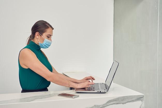 Mujer latina con cubrebocas trabajando en su ноутбука en la recepcion