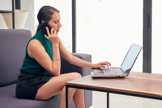 Mujer latina hablando por telefono mientras trabaja en su casa con su computadora