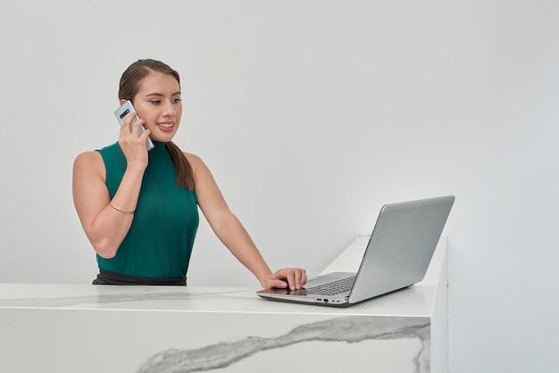 Mujer latina hablando por telefono mientras trabaja en su ноутбук