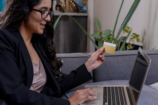 Mujer latina haciendo compras en su computadora portatil y pagando con tarjeta de credito desde casa