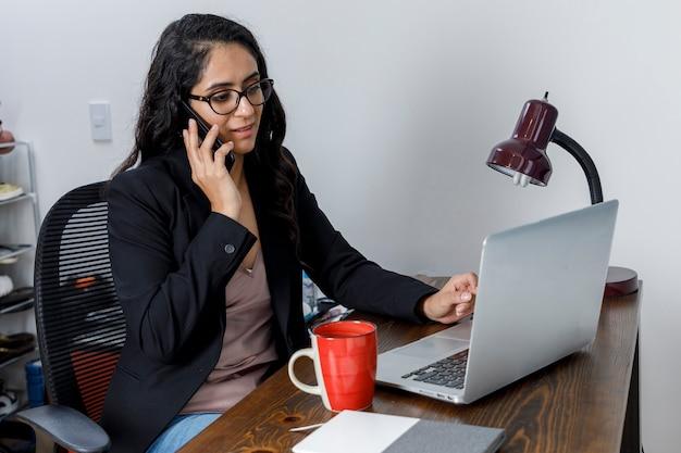 Mujer molsta hablando por telefono mientras trabaja desde cas debido a la pandemia