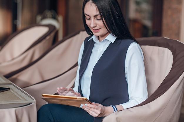 Mujer tocando una 태블릿 naranja
