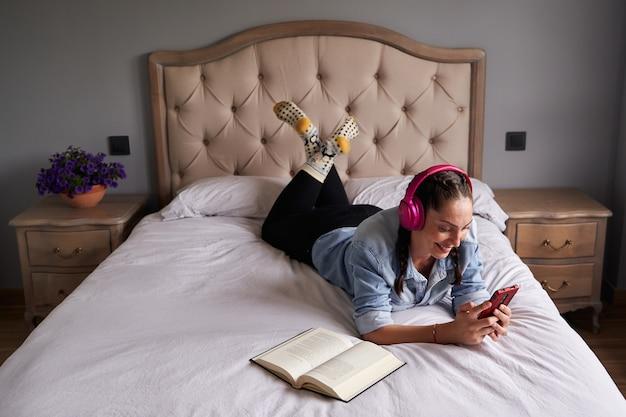 Mujer tumbada en la cama escuchando musica con auriculares junto a un libro