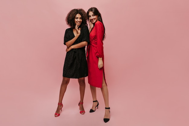 Mulatto beautiful girl in dark polka dot dress and bright heels smiling, looking into cameara and posing with trendy girl in red clothes