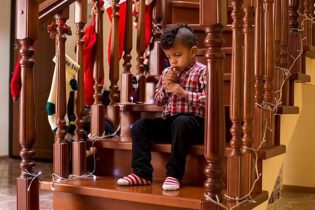Ребенок-мулат играет на духовом инструменте мальчик играет на флейте во время рождества, не торопитесь, маэстро, так что вы ...