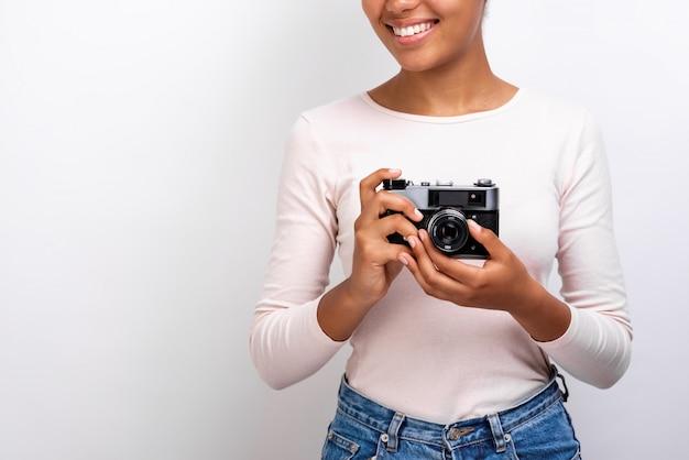彼女の手で写真のカメラを持ってムラート旅行者の女の子