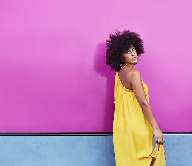 アフロヘアーのムラートの女性は黄色のドレスを着ています Premium写真
