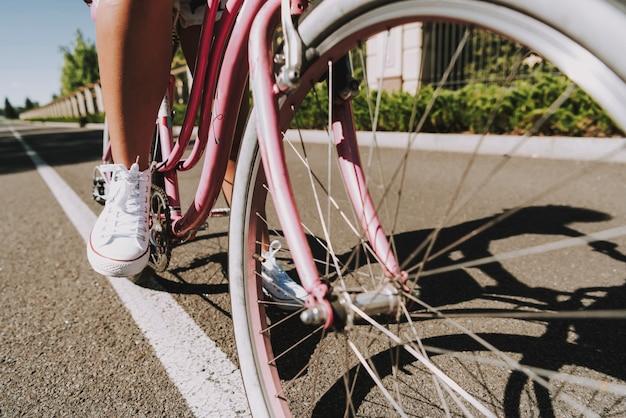 閉じる。 mulattoの女の子が路上で自転車のペダルに足。