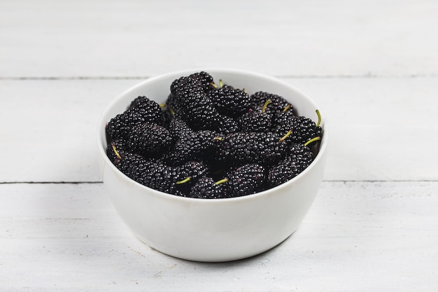 Mulberry fruit in white bowl on wood table
