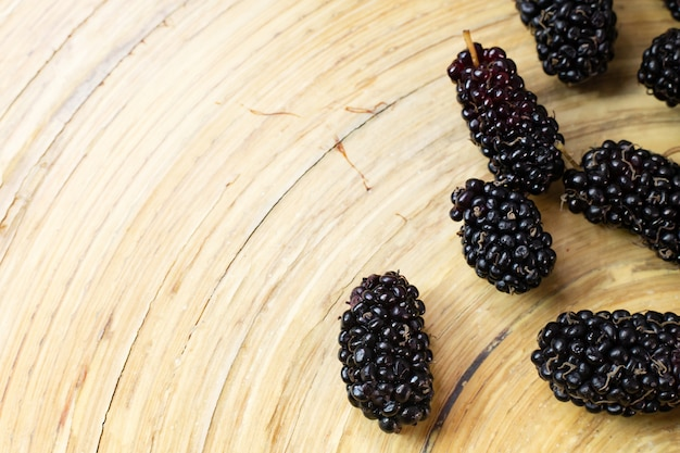 The mulberry fruit in white bowl on wood table.