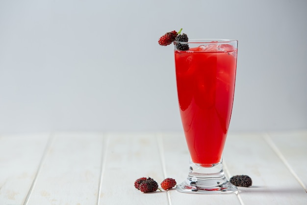 Mulberry juice on white wooden surface