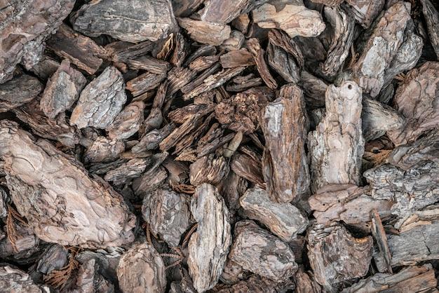 Мульчирование клумбы мульчей из сосновой коры в качестве фона куча сухих кусочков коры сосны