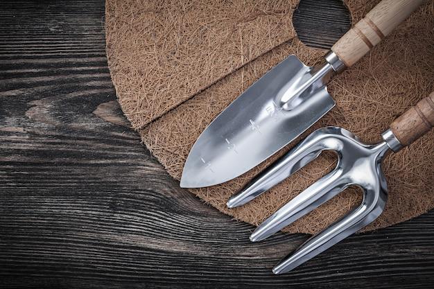 Mulching mat shovel trowel fork on wood board gardening concept