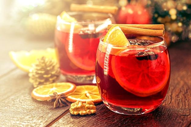 クリスマスの色とライトの素朴な木製のテーブルにスパイスとクリスマスフルーツとホットワイン